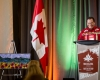 Robert Bernard at the podium on stage next to the Canadian flag at GoMedia 2017